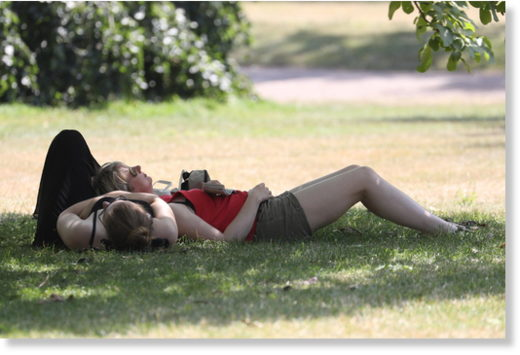 People lie in a park under 30+ degrees Celsius in London, July 25th 2019